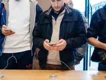 Мужские друзья сравнивая покупающ самое последнее iphone x Стоковые Изображения RF