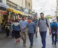 Мужские еврейские студенты нося крышки черепа и в переговоре по мере того как они делают их путь через занятый уличный рынок Maha стоковое изображение rf