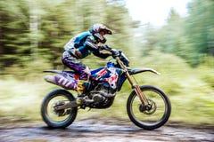 Мужские езды гонщика мотоцикла спортсмена в древесинах Стоковое фото RF