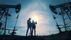 Мужские инженеры смотря нефтяную вышку на поле видеоматериал