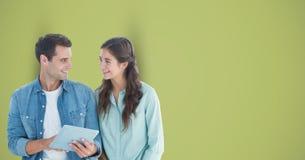 Мужские и женские битники с цифровой таблеткой против зеленой предпосылки стоковое фото rf