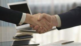 Мужские и женские деловые партнеры подписывая контракт и тряся руки, приобретение сток-видео
