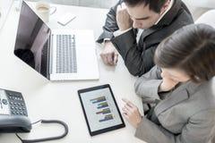 Мужские и женские деловые партнеры анализируя статистически ежегодник r стоковые изображения