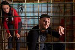 Мужские и женские жертвы заключенные в турьму в клетке металла Стоковые Изображения RF