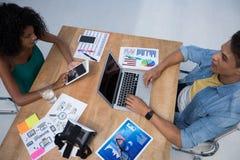 Мужские и женские исполнительные власти работая в офисе стоковые изображения