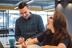 Мужские и женские коллеги смеясь над на офисе Стоковое Изображение