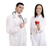 Мужские и женские доктора держа яблоко и пилюльки - изображение запаса Стоковые Фотографии RF