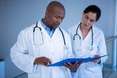 Мужские и женские доктора имея над доской сзажимом для бумаги в коридоре Стоковая Фотография RF
