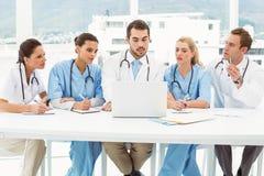 Мужские и женские доктора используя компьтер-книжку Стоковые Фото