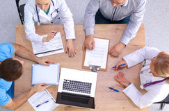 Мужские и женские доктора работая на отчетах внутри Стоковое фото RF