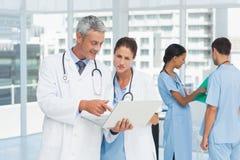 Мужские и женские доктора работая на отчетах Стоковые Фото