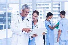 Мужские и женские доктора работая на отчетах Стоковые Изображения RF