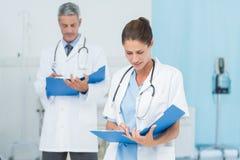 Мужские и женские доктора работая на отчетах Стоковое Изображение RF