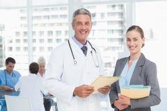 Мужские и женские доктора работая на отчетах Стоковое Фото