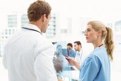 Мужские и женские доктора рассматривая рентгеновский снимок Стоковое Изображение RF