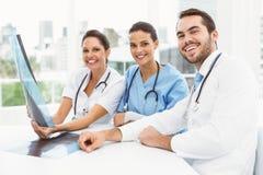 Мужские и женские доктора рассматривая рентгеновский снимок Стоковая Фотография RF