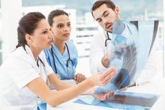 Мужские и женские доктора рассматривая рентгеновский снимок Стоковые Изображения