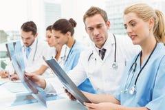Мужские и женские доктора рассматривая рентгеновский снимок Стоковые Фотографии RF