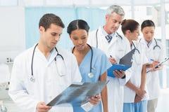 Мужские и женские доктора рассматривая рентгеновский снимок Стоковое Изображение