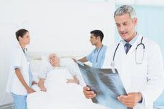 Мужские и женские доктора рассматривая рентгеновский снимок Стоковое фото RF