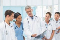 Мужские и женские доктора рассматривая рентгеновский снимок Стоковая Фотография