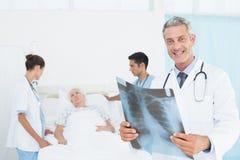 Мужские и женские доктора рассматривая рентгеновский снимок Стоковые Изображения RF