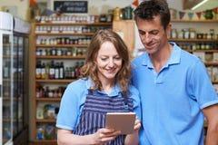 Мужские и женские работники в магазине деликатеса используя цифров Tabl стоковая фотография rf