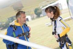 Мужские и женские parachutists под воздушными судн крыла Стоковые Фото