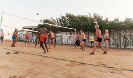 Мужские кавказцы, арабы, африканцы играя волейбол на пляже на заходе солнца Египет Hurghada Золотой 5-ое октября 7, 2016 стоковая фотография rf