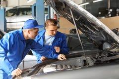 Мужские механики исправляя автомобиль в пункте обслуживания стоковые фото