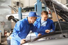 Мужские механики исправляя автомобиль в пункте обслуживания стоковое фото