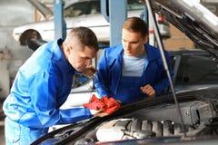Мужские механики исправляя автомобиль в пункте обслуживания стоковые изображения