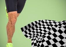 Мужские ноги бегуна на старте выравниваются с checkered флагом против зеленой предпосылки Стоковая Фотография