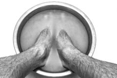 Мужские ноги в тазе с мустардом витают его ноги, на белой естественной предпосылке стоковое фото