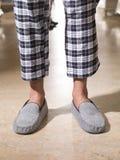 Мужские ноги нося серые тапочки спальни стоковые изображения rf