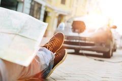 Мужские ноги с картой на их смотря на автомобиль Стоковое Фото