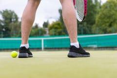 Мужские ноги ` s теннисиста во время игры на суде зеленой травы o Стоковое Изображение RF