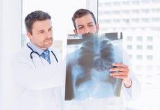 Мужские доктора рассматривая рентгеновский снимок в медицинском офисе Стоковые Фото