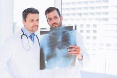 Мужские доктора рассматривая рентгеновский снимок в медицинском офисе Стоковое фото RF