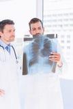 Мужские доктора рассматривая рентгеновский снимок в медицинском офисе Стоковые Фотографии RF