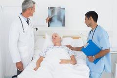 Мужские доктора рассматривая рентгеновский снимок с пациентом Стоковая Фотография RF