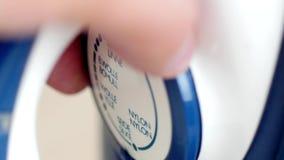 Мужские пальцы поворачивая регулятор температуры утюга сток-видео
