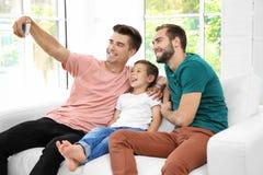 Мужские пары гомосексуалиста при приемный сын принимая selfie стоковая фотография
