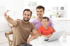 Мужские пары гомосексуалиста при приемный сын принимая selfie стоковая фотография rf