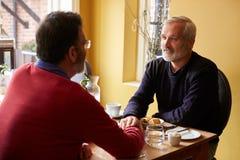 Мужские пары держа руки на ресторане, над взглядом плеча стоковые изображения