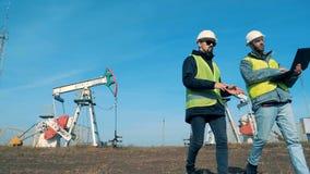 Мужские работники energetics идут далеко от масляных насосов, нефтяных вышек Нефтедобывающая промышленность, нефтяная промышленно видеоматериал