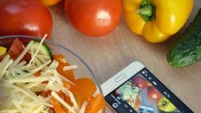 Мужские руки варя кухню салата дома Молодой человек подготавливая vegetable еду и используя поднимающее вверх smartphone близкое сток-видео