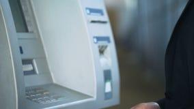 Мужские руки входя в код штыря на клавиатуре ATM, разделяя деньги от учета акции видеоматериалы