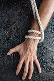 Мужские руки вытягивают веревочку на черной предпосылке стоковое фото