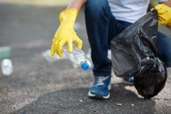 Мужские руки в желтых резиновых перчатках кладя отход домочадца в малую и черную сумку ящика снаружи Стоковое Изображение RF
